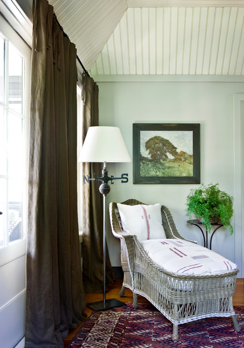 Cozy Corner with Wicker Chaise and Landscape Paintings