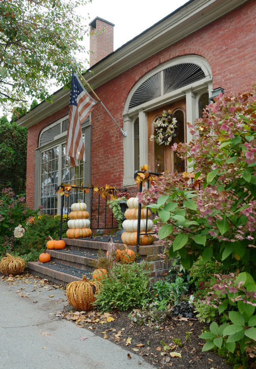 Historic Brick Home Exterior Decorated for Fall with Pumpkins