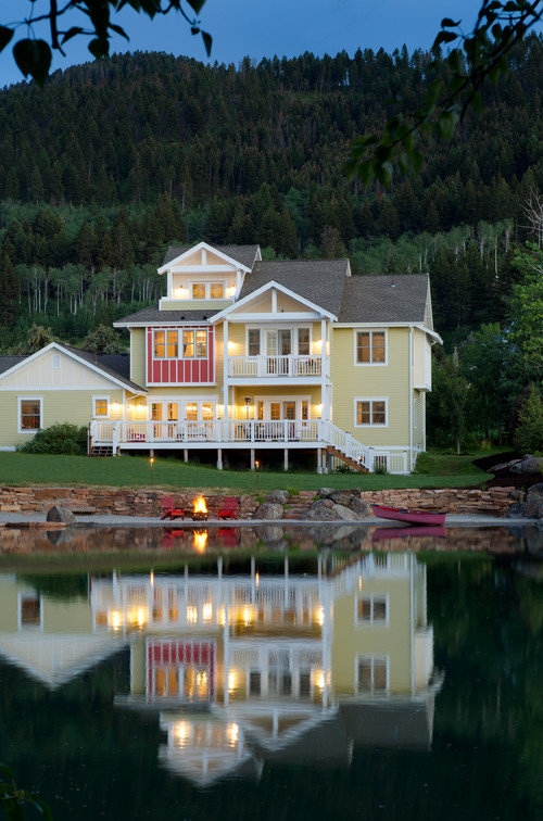 Yellow Lakeside Home Lit Up at Night