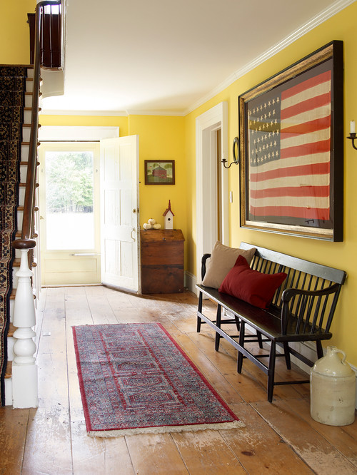 Vintage Farmhouse Entry with Wide-Plank Floors and Yellow Walls