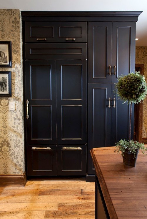 Refrigerator concealed with black kitchen cabinet doors