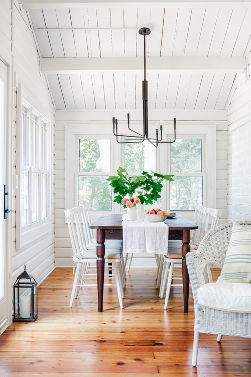 White dining room with wood floors and farmhouse table