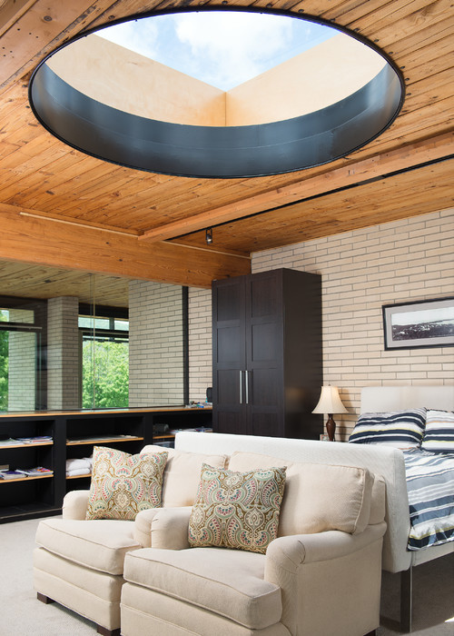 Round skylight in wood planked bedroom ceiling