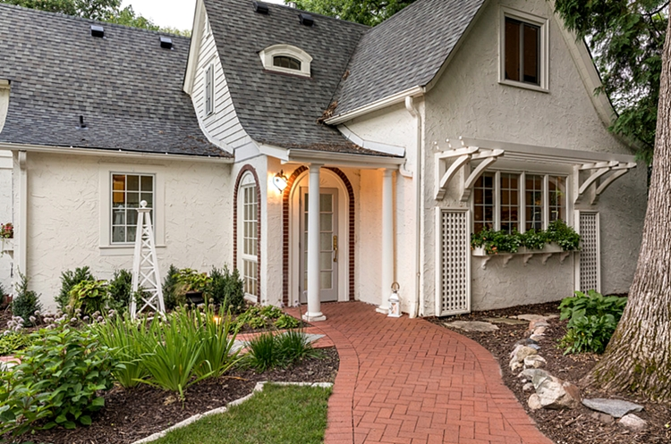 White Stucco Cottage with Brick Walkway and Unique Garden