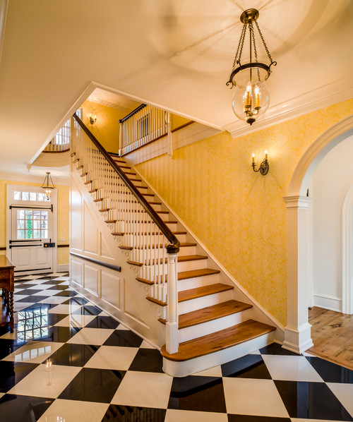 Grand staircase with checkerboard floor in entryway