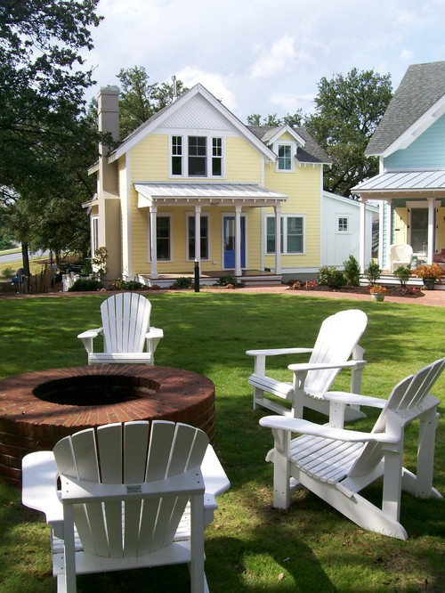 Yellow Farmhouse with White Adirondack Chairs around Fire Pit