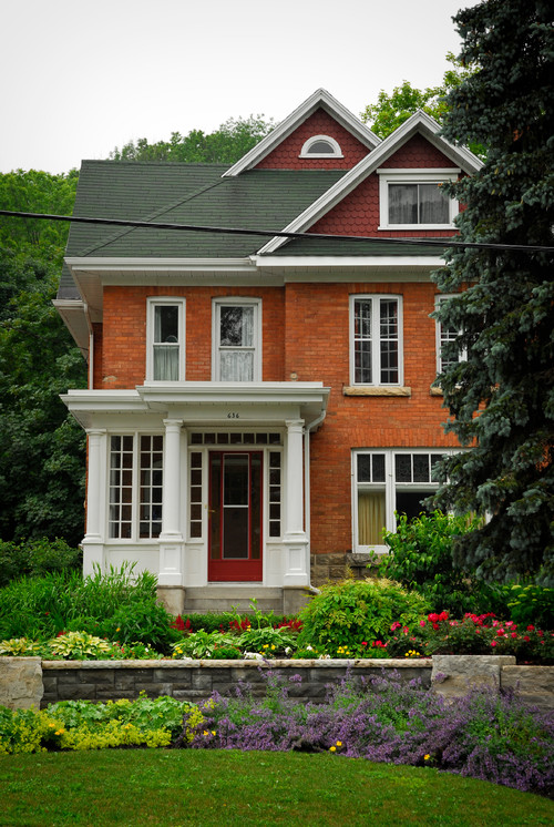 Classic red brick house with white trim and green roof