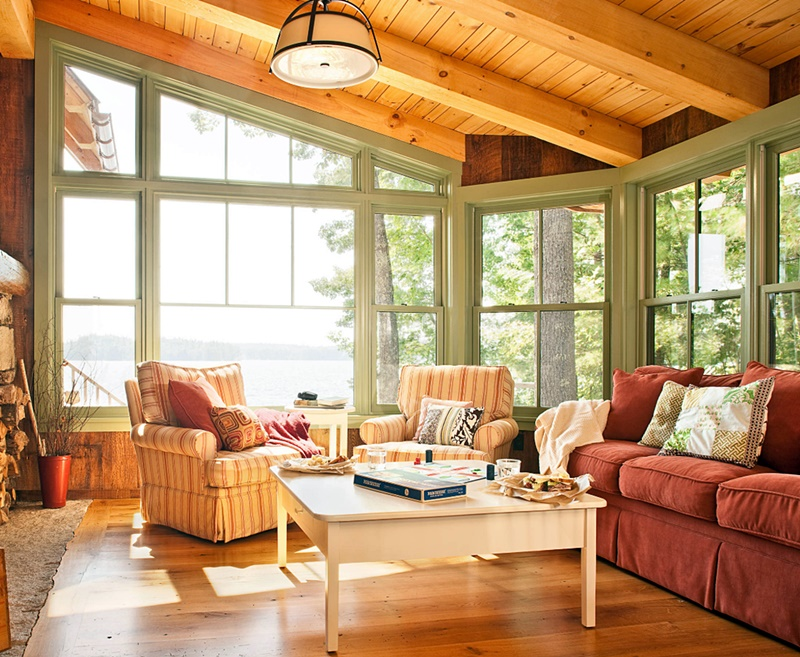 Rustic Cabin Living Room with Stone Fireplace and Wall of Windows
