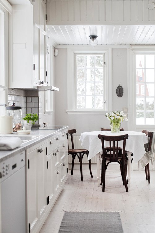 White Farmhouse Kitchen with Round Table and Wood Chairs