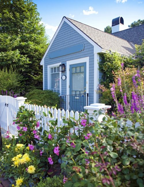 New England garden cottage with white picket fence and messy flowers