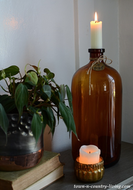 Brown Bottle with Candles and Philodendron