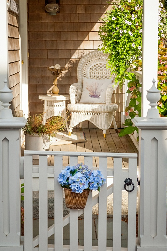 Cottage Porch with White Wicker Rocking Chair and Picket Fence