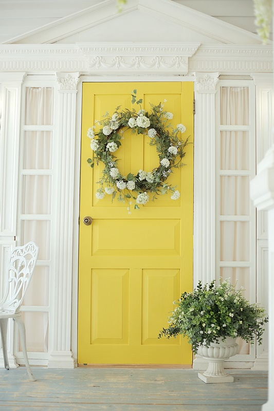 Beautifully decorated farmhouse look. Bright yellow door and a spring greenery wreath of flowers