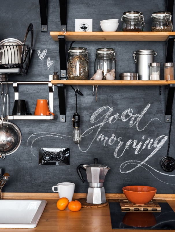 "Design of modern kitchen in loft and rustic style. Wooden Shelves with different jars on a black wall with chalk ""Good Morning""."