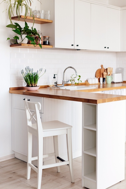 Modern white u-shaped kitchen in scandinavian style. Open shelves in the kitchen with plants and jars. Spring decoration