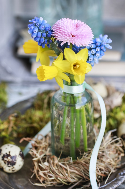 Bouquet of tiny spring flowers in glass vase. Hay wreath around. Party decor