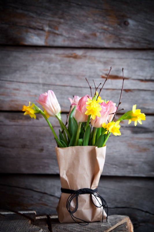 Springtime flower bouquet with tulips and daffodils in brown paper bag