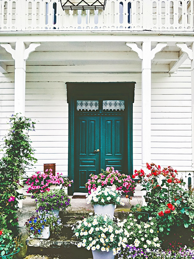 White wooden country house entrance door terrace cozy exterior with flowers design decoration and balcony retro style traditional building