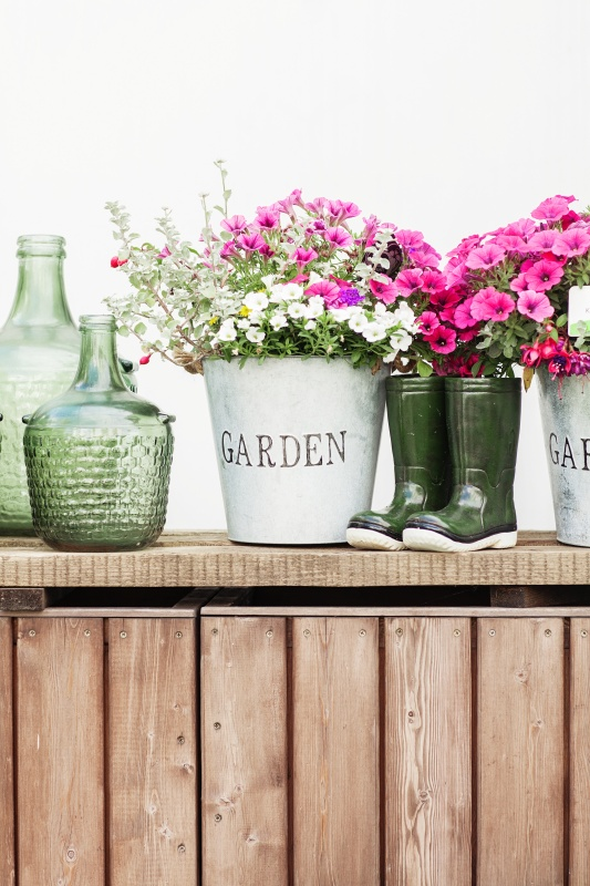 Country Flower Vignette with Boots, Pink Flowers, and Green Glass Bottles