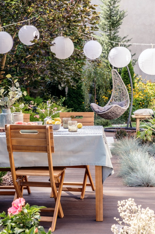 White paper lamps above garden table with chairs on stylish terrace with wooden floor and plants