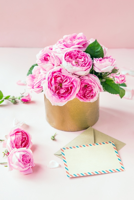 Tender pink tea roses bouquet in vintage pot, blank of greeting card and craft paper envelope on pink background.  Summer, spring flowers.