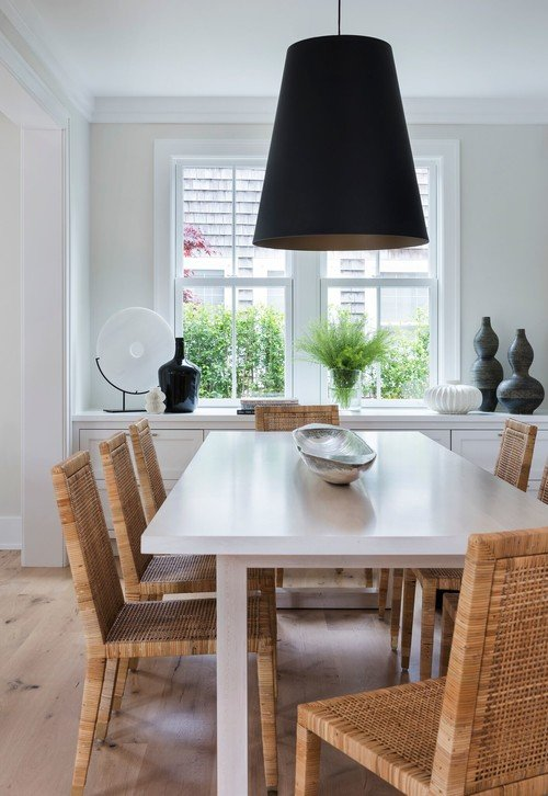 Beach Style Dining Room with Rattan Chairs and Large Black Pendant Light