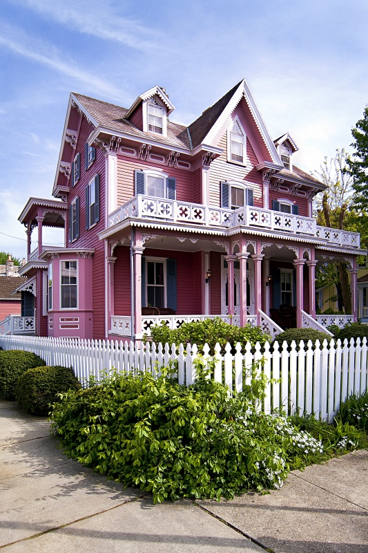 Beautiful pink Victorian house with porch and balcony surrounded by a white picked fence.