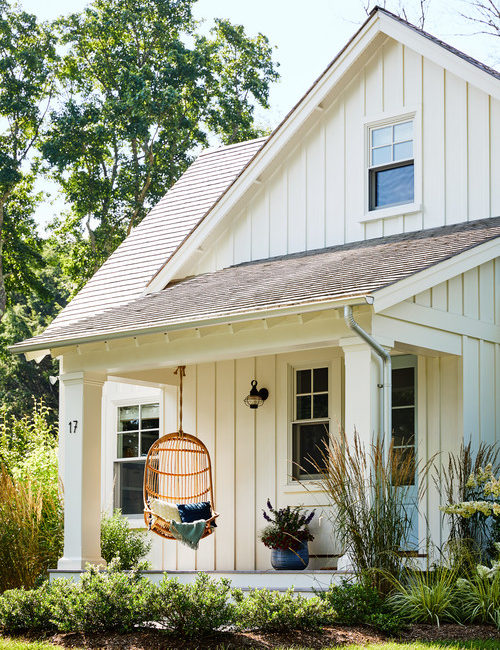 Charming White Porch with Hanging Rattan Chair
