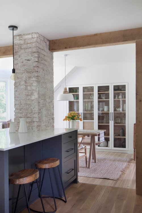 Dark blue kitchen island and white washed brick chimney in renovated farmhouse