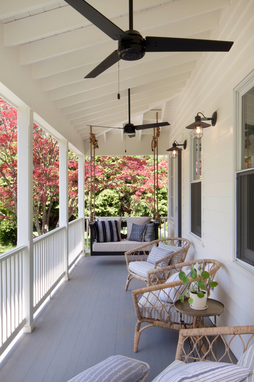 Renovated Farmhouse porch with hanging swing and boho chic chairs