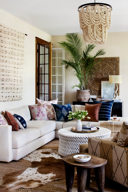 Mediterranean style decorating with wood bead chandelier and large palm plant