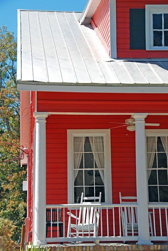 Red House with White Rocking Chairs on Front Porch