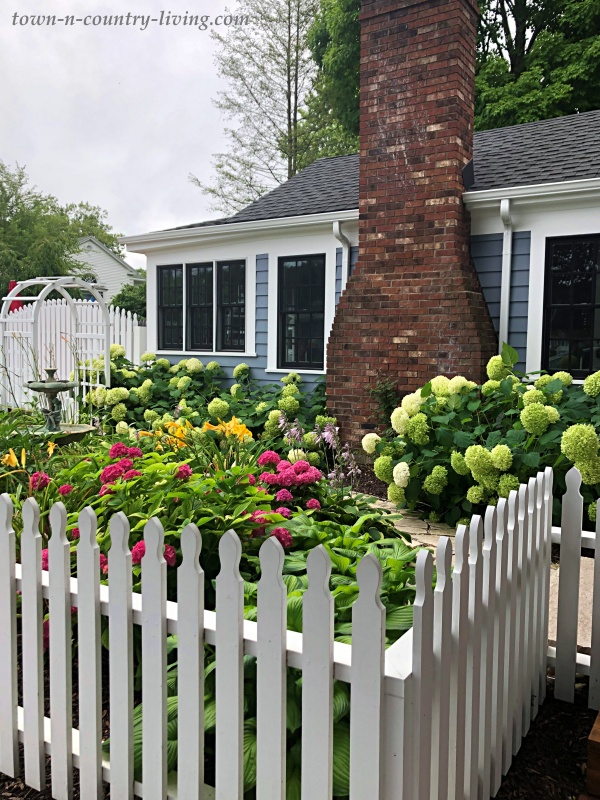 Flowering Home Garden with White Picket Fence