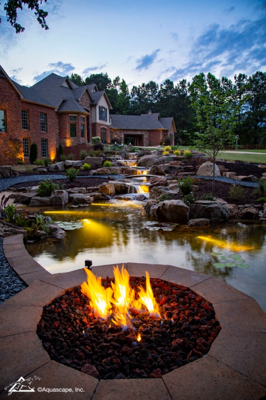 Fire Pit by Pond and Waterfall at Night