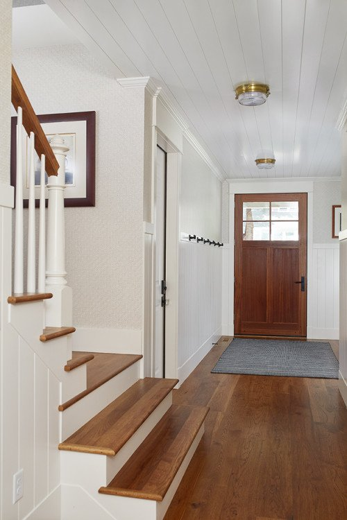 White and Wood Entryway with Staircase in Cozy Lake Cottage