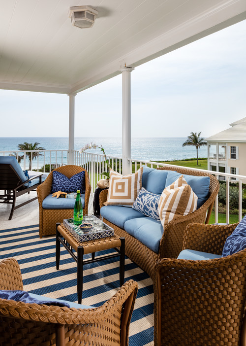 Summer Porch by the Sea with Wicker Furniture and Rug with Blue and White Stripes