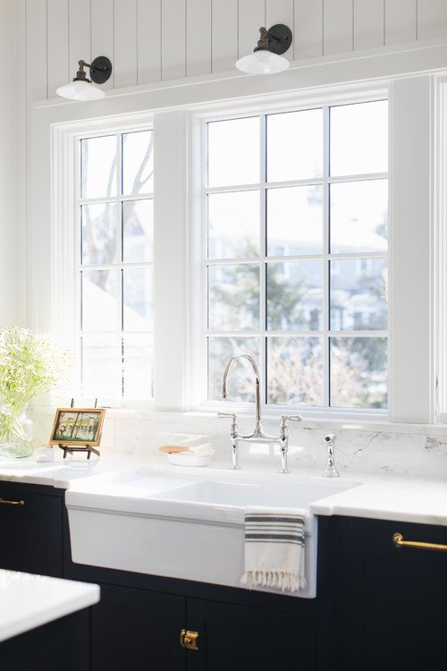 White Farmhouse Sink with Black Kitchen Cabinets and White Marble Counter Tops