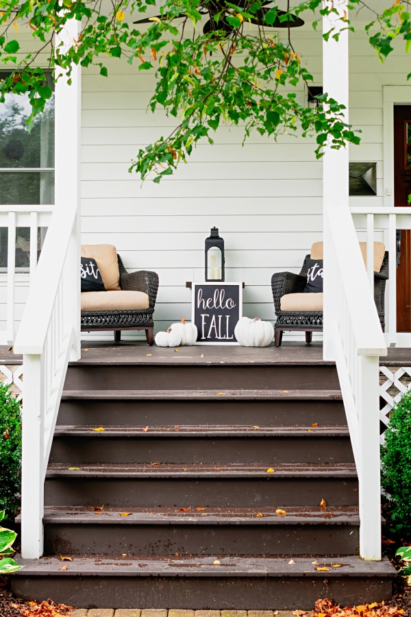 Stylish fall decorations in black and white on traditional front porch - hello fall