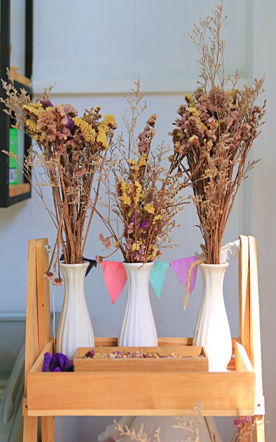 Dried flowers in vase decoration on wood shelf