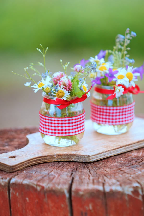Beautiful summer wild flowers in a nice glass jar on a wooden background. Summer bouquet. Bunch of flowers.
