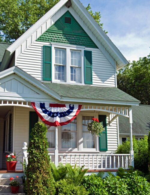 Green and White Victorian House with Patriotic Porch