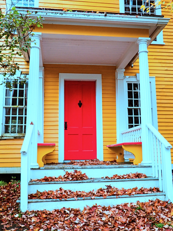 Yellow New England house and porch with red door and fall leaf covered white steps