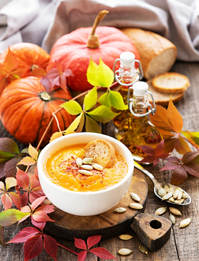 Bowl of pumpkin soup, fresh pumpkins and autumn leaves on rustic wooden background