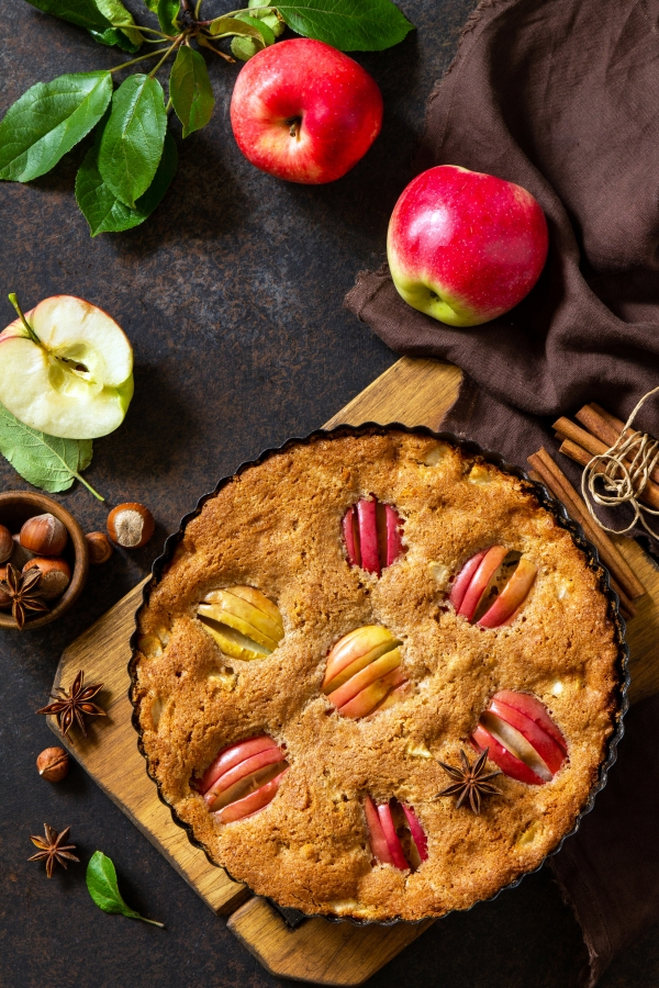Apple baking seasonal. Apple pie with hazelnut and cinnamon on a rustic wooden table.