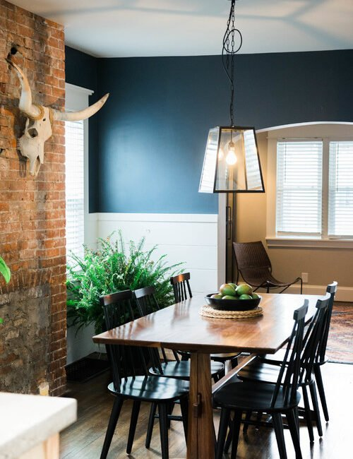 Cottage Dining Room with Exposed Brick and Dark Blue Walls
