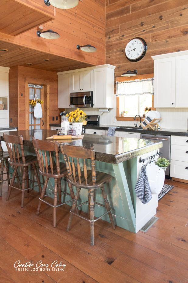 Cabin Style Kitchen with Wood Plank Walls and White Cabinets