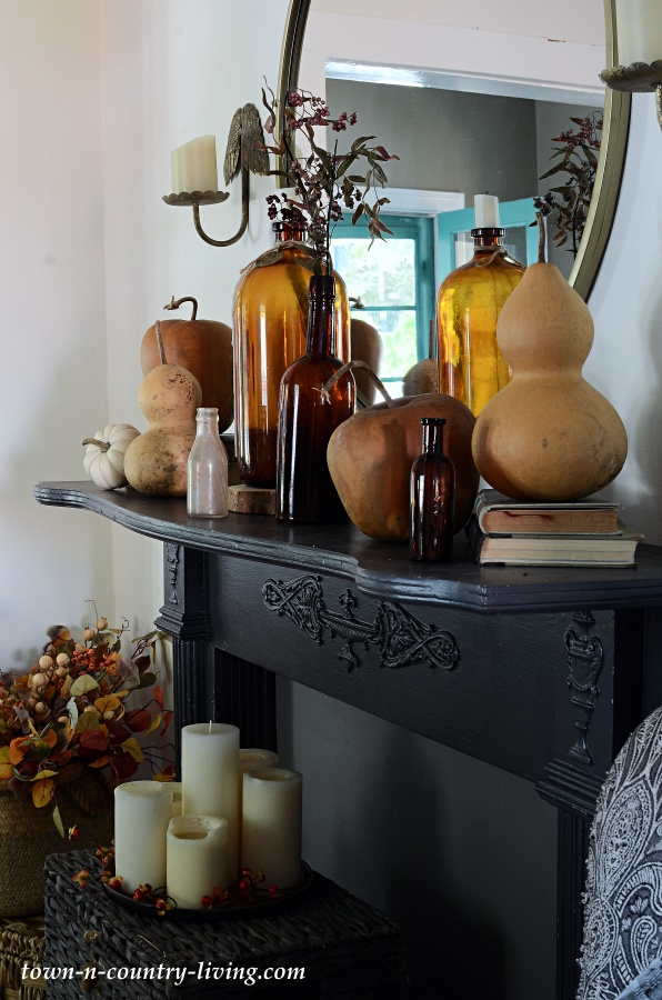 Fall Mantel with Amber Bottles and Dried Gourds