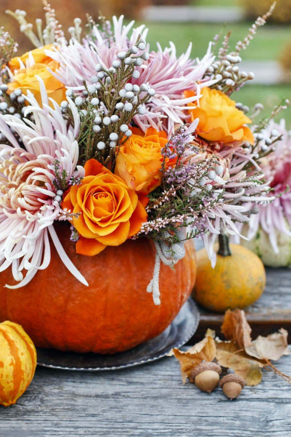 Bouquet of fall flowers in pumpkin. Autumn decor