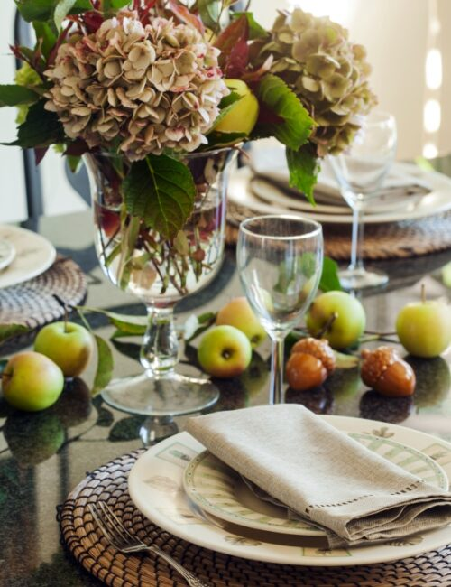 Fall table setting with apples and autumn flowers