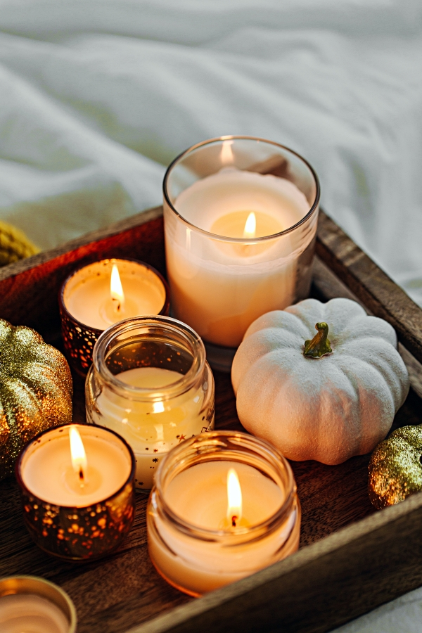 Gathering of candles and mini pumpkins on a wooden tray